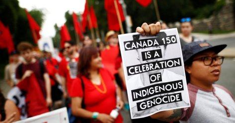"An indigenous rights activist holds a sign reading ""Canada 150 is a Celebration of Indigenous Genocide"", in Toronto"